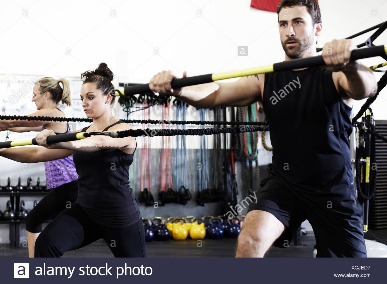 Persone che lavorano in palestra con esercizio bar e cavo di resistenza Immagini Stock
