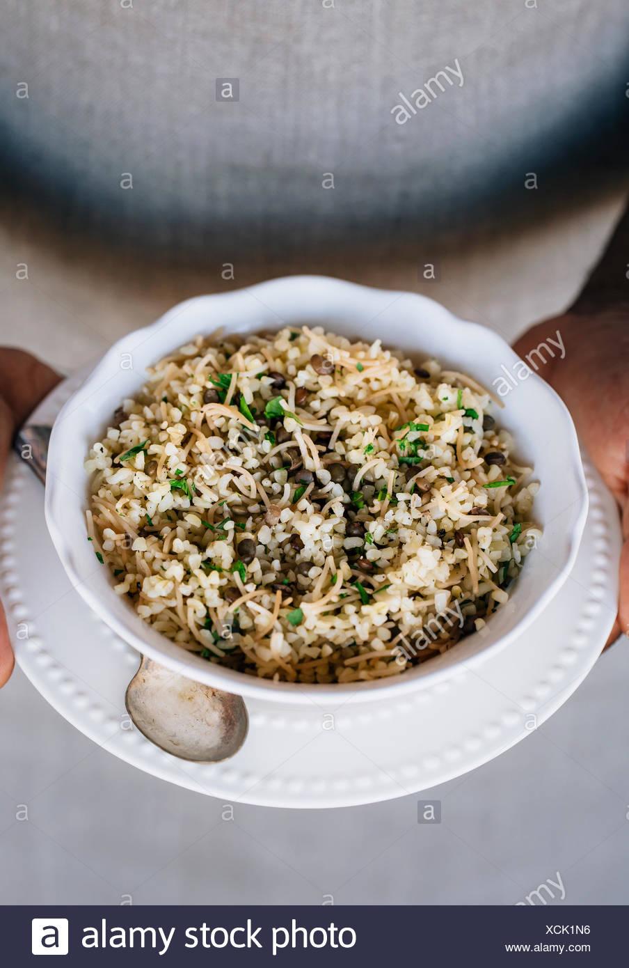 Una tazza di bulgur pilaf mescolato con le lenticchie e le erbe fresche sono nelle mani di un uomo che indossa un grembiule. Immagini Stock
