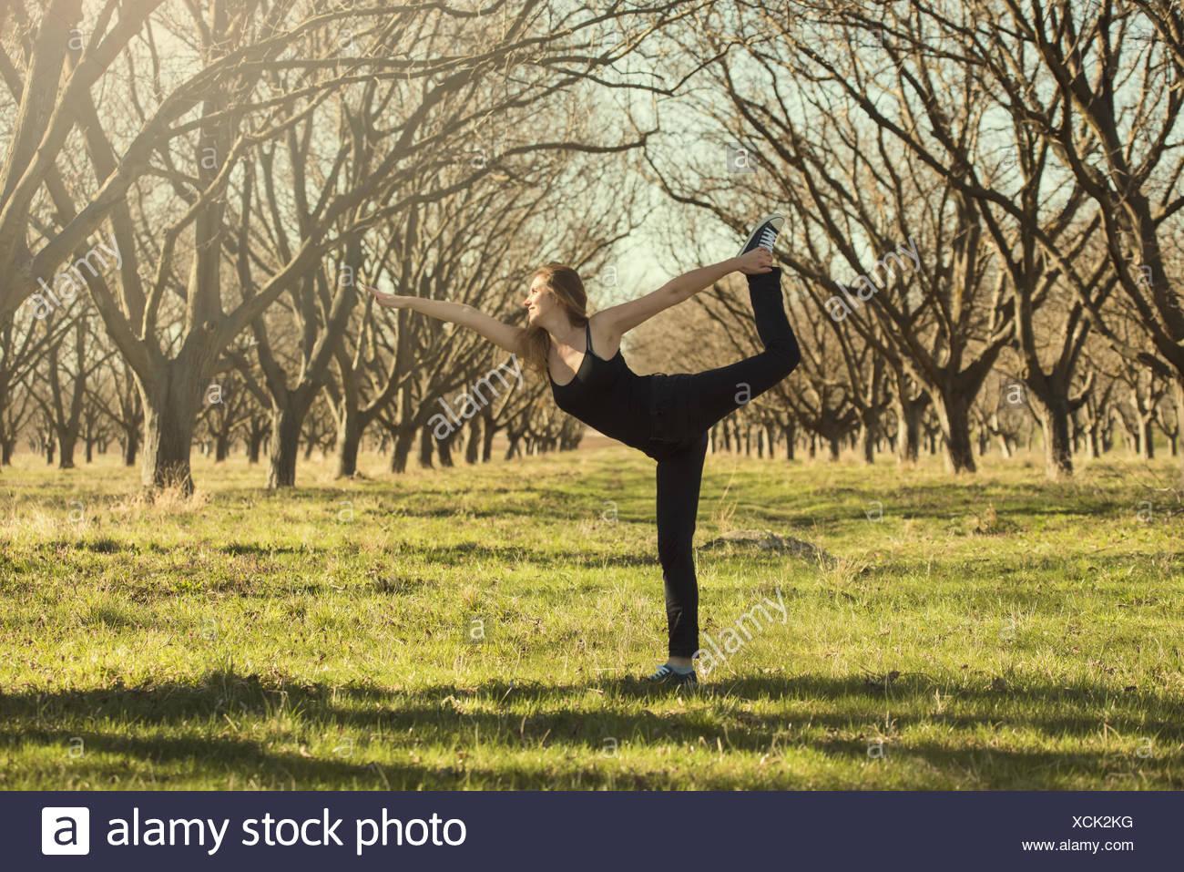 Donna in piedi nel frutteto fare yoga, Stara Zagora, Bulgaria Foto Stock