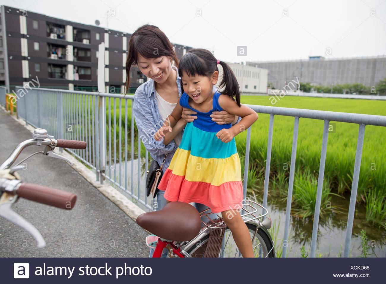 Una madre sollevando la figlia su una bicicletta. Immagini Stock
