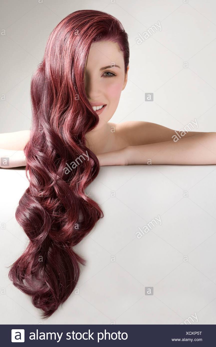 Bella donna con rosso lungo i capelli tinti contro uno sfondo grigio Immagini Stock