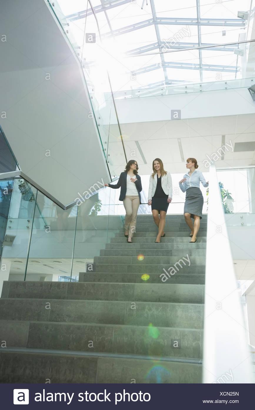 Felice imprenditrici a conversare mentre si sta spostando verso il basso le fasi in office Immagini Stock