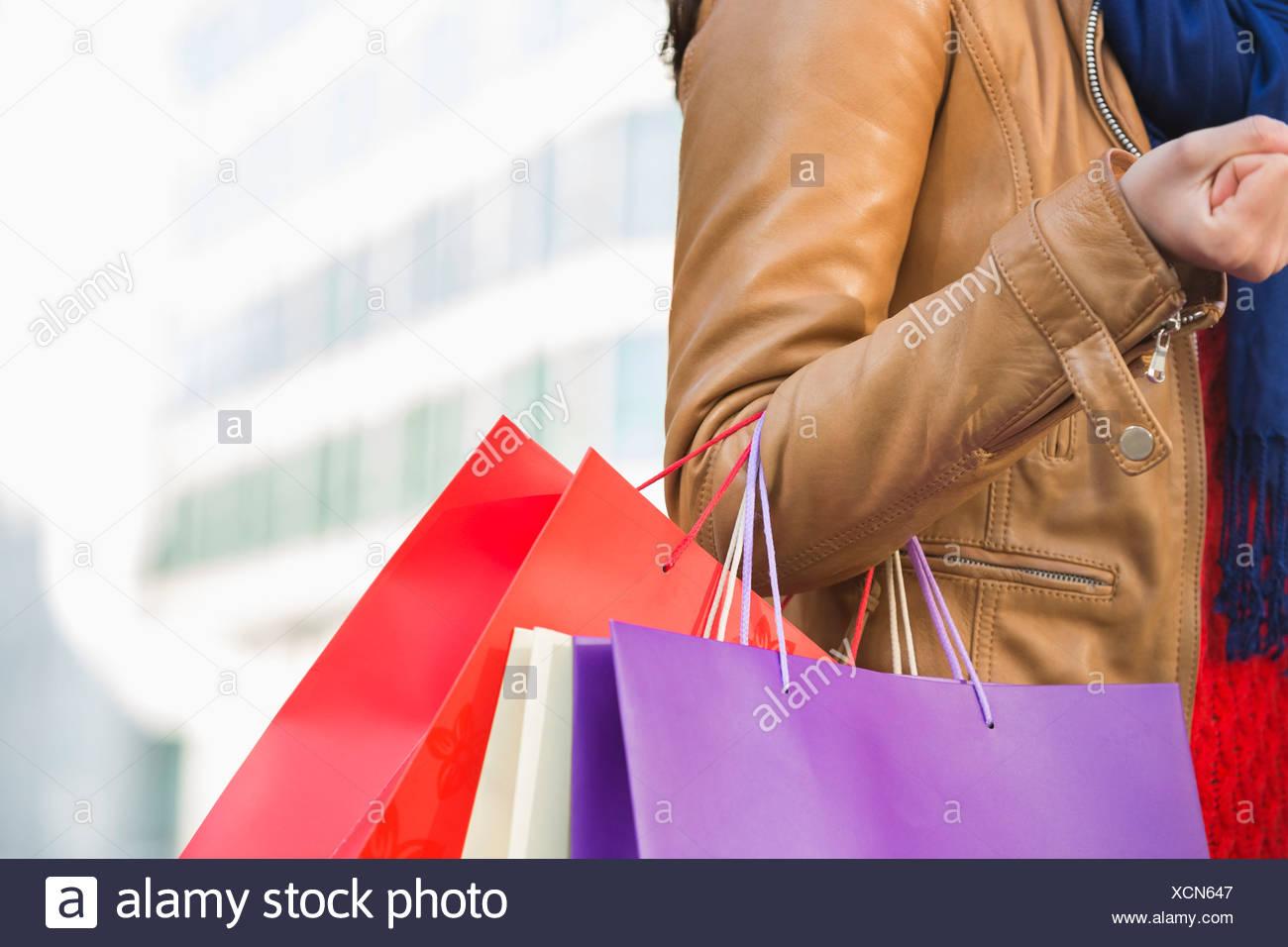 La sezione centrale della donna il trasporto delle borse della spesa Immagini Stock