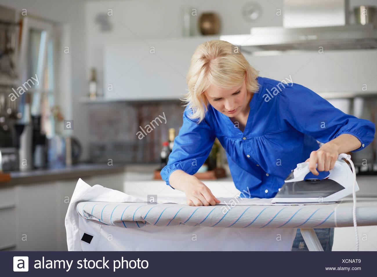 Donna con cautela il marito di stiratura shirt Immagini Stock