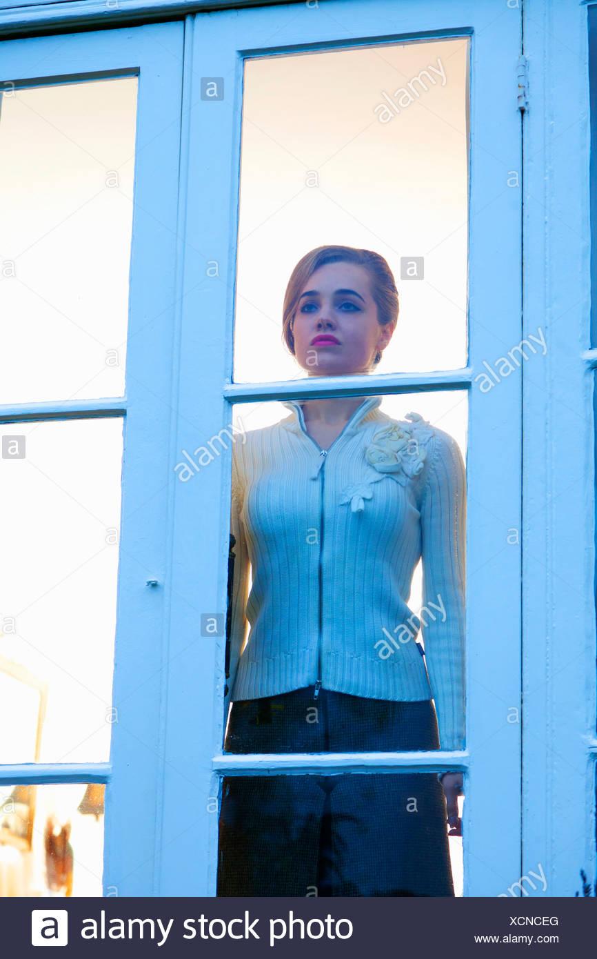 Donna che guarda fuori porta in vetro Immagini Stock