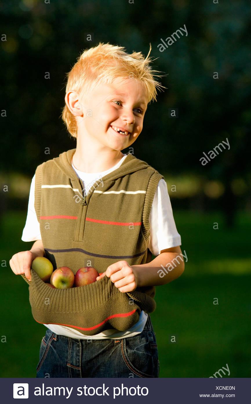 Ragazzo con parte superiore per raccogliere le mele, sorridente Immagini Stock