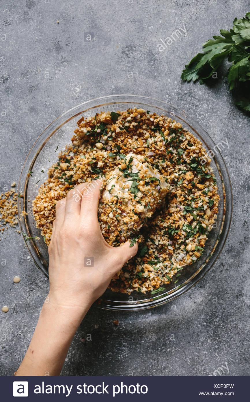 Passo 3 di 4: una donna è fotografato come ella è il rivestimento di un filetto di pesce con fatti in casa pane grattugiato. Immagini Stock
