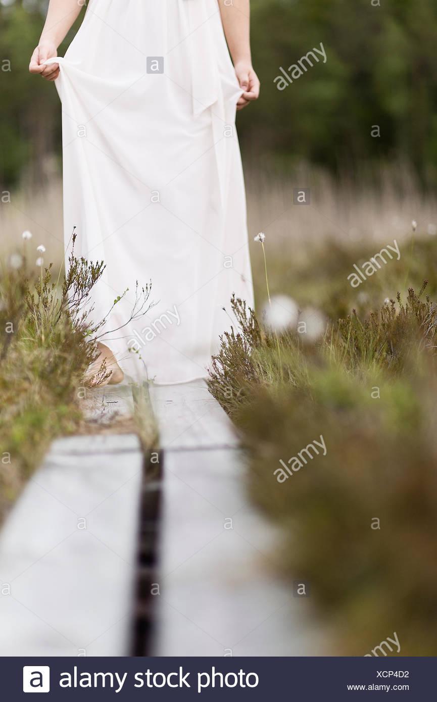 La Svezia, Vastmanland, ragazza adolescente (16-17) in abito bianco in piedi sul cavalcavia in Prato Immagini Stock
