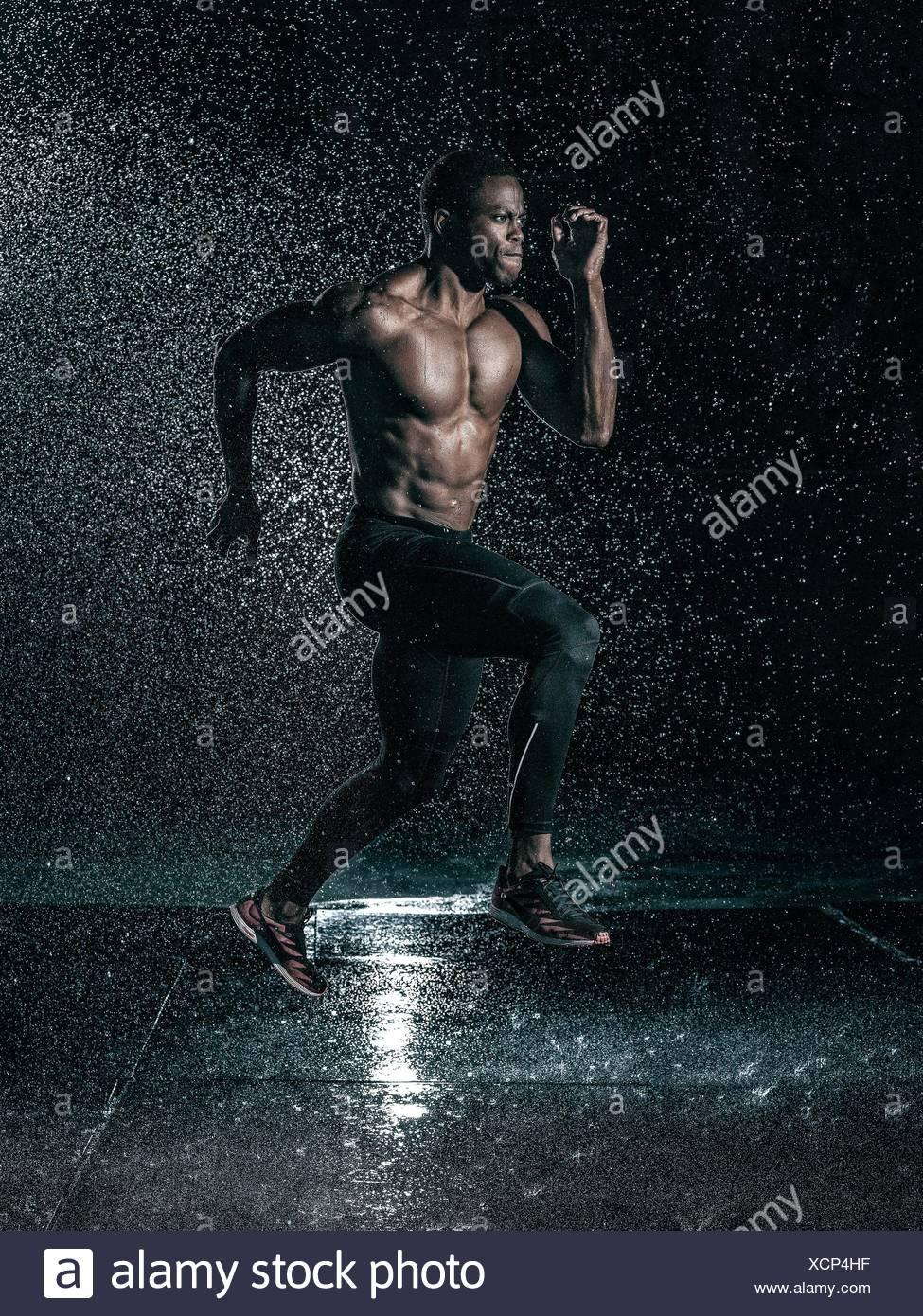 Metà uomo adulto, esterni in esecuzione in caso di pioggia Immagini Stock