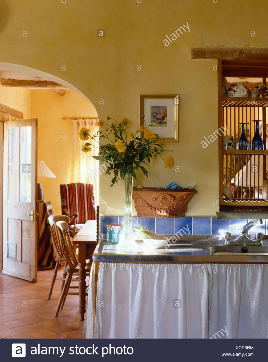 Drappi bianchi su isola di unità con lavello in cucina con ...