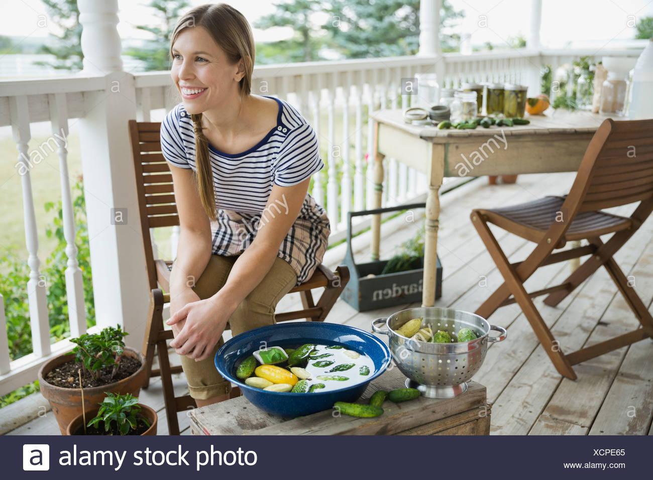 La donna il lavaggio della verdura sul portico Immagini Stock