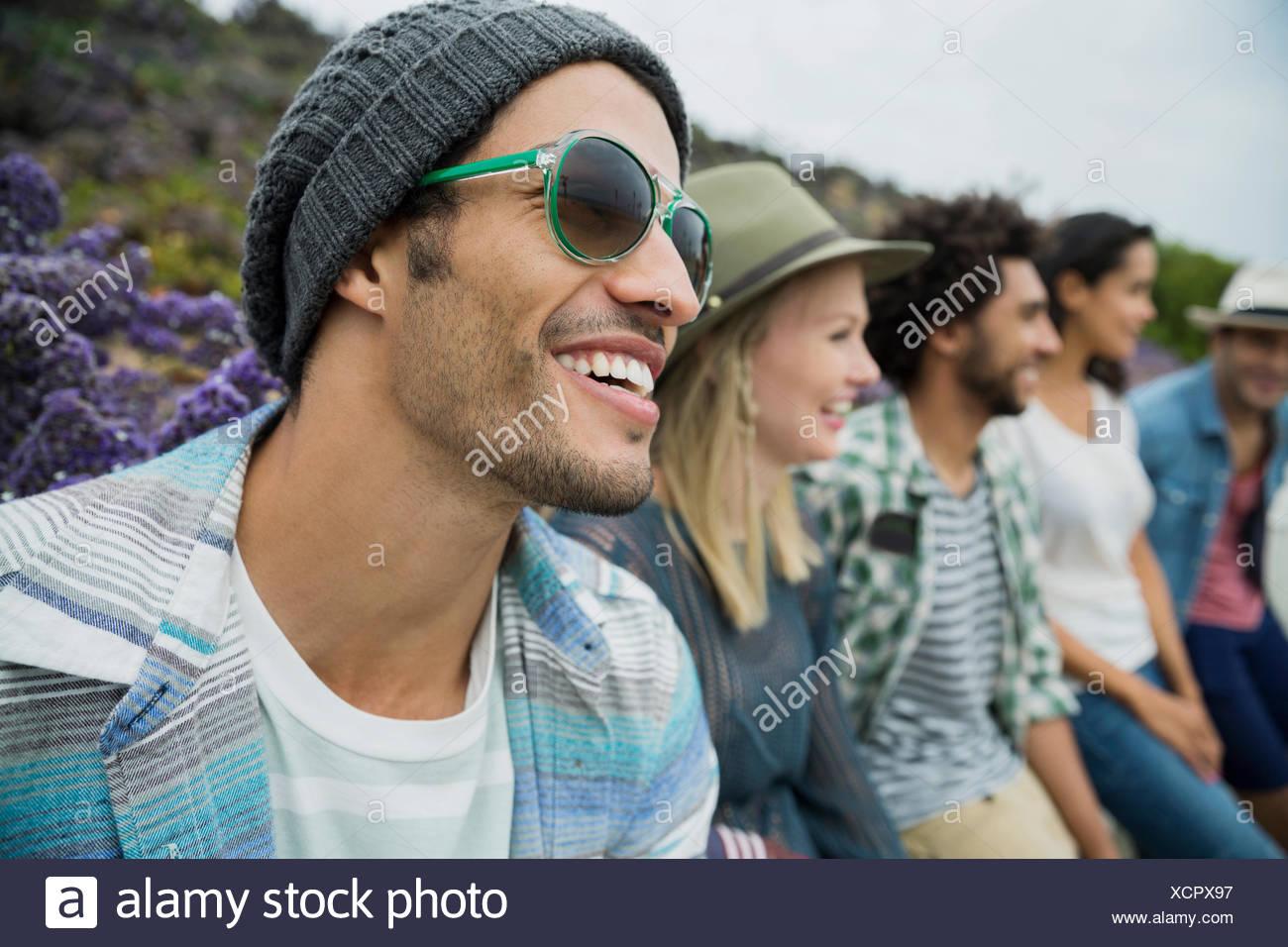 Sorridente amici seduti in una riga Immagini Stock