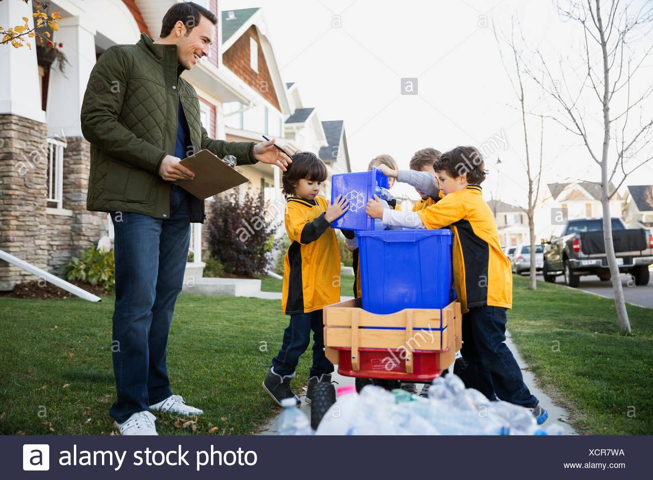 Autobus e i ragazzi del team sportivo raduno quartiere di riciclaggio Immagini Stock