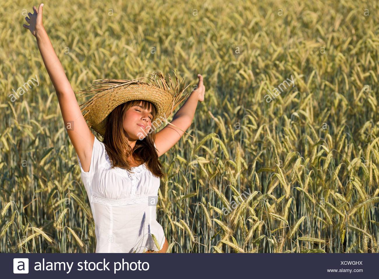 Felice donna con cappello di paglia nel campo di grano Foto ... bf1741f97602