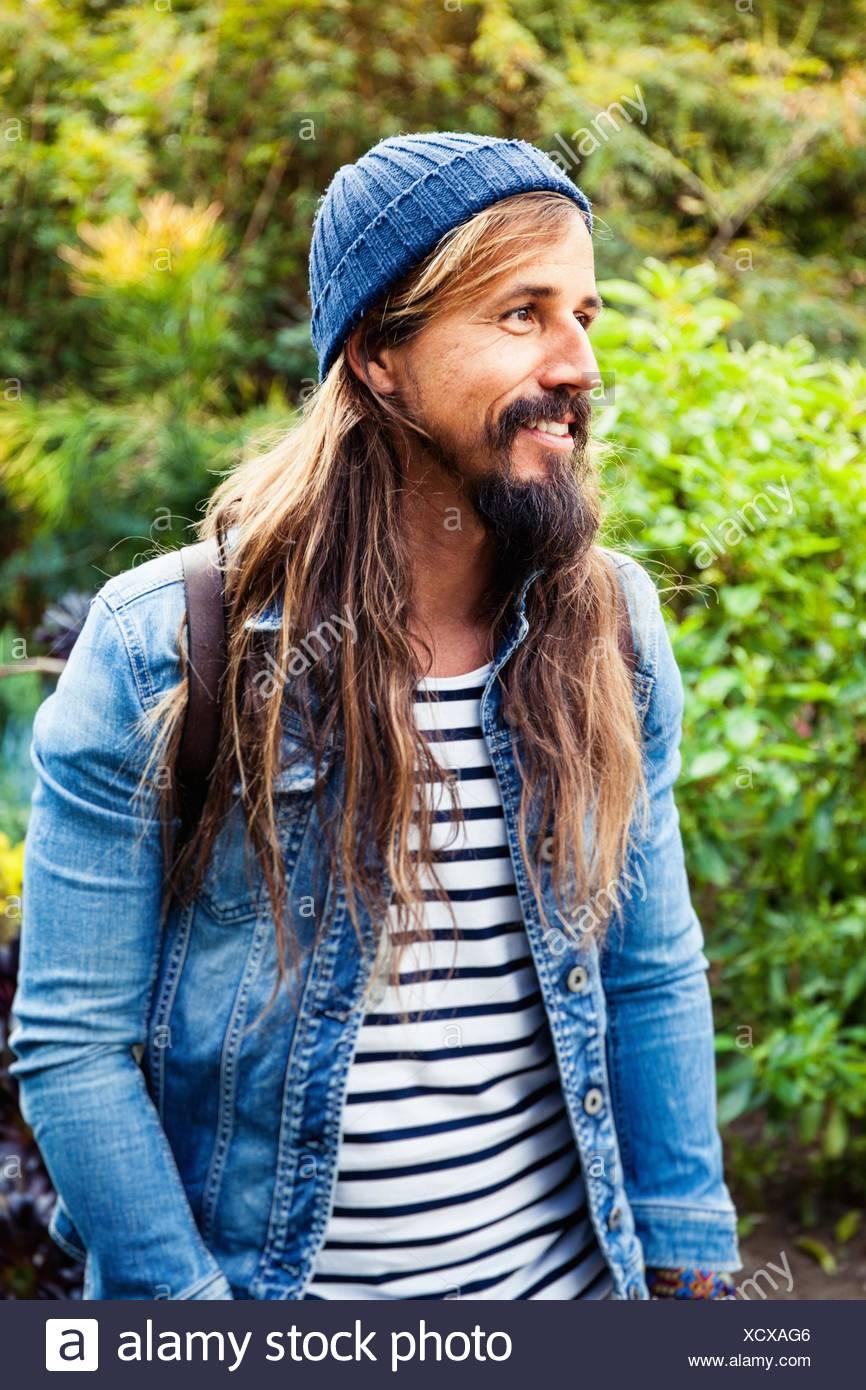 Metà uomo adulto con capelli lunghi, indossando hat Immagini Stock