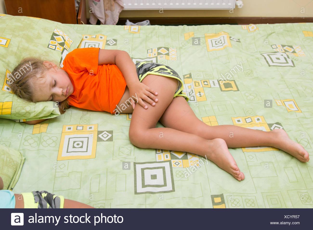 Bambina è dormire sul suo fianco sul grande letto senza una coperta Immagini Stock