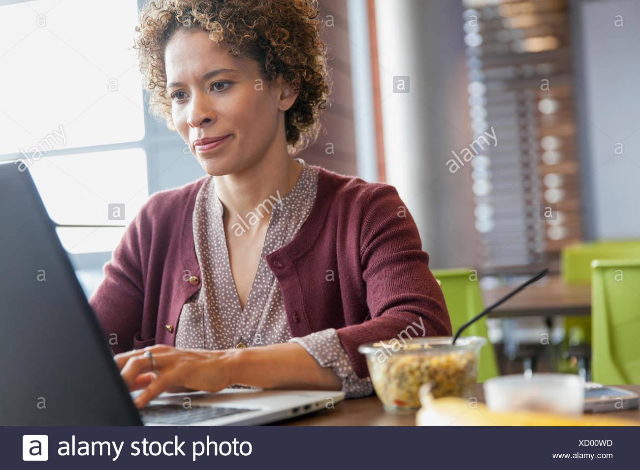 Donna con snack presso il suo computer portatile. Immagini Stock