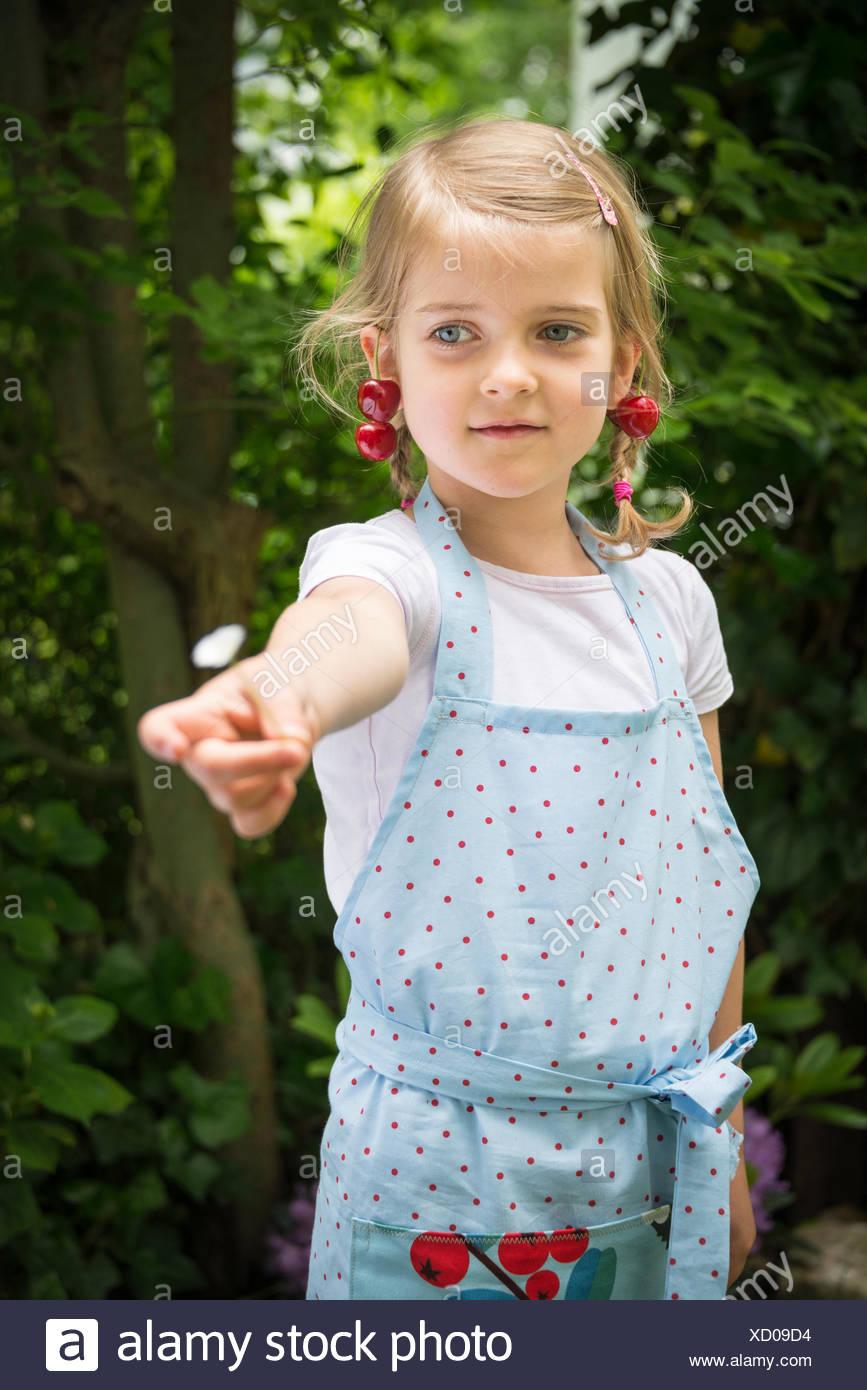 Bambina con ciliegie penzolante dal suo orecchio Immagini Stock