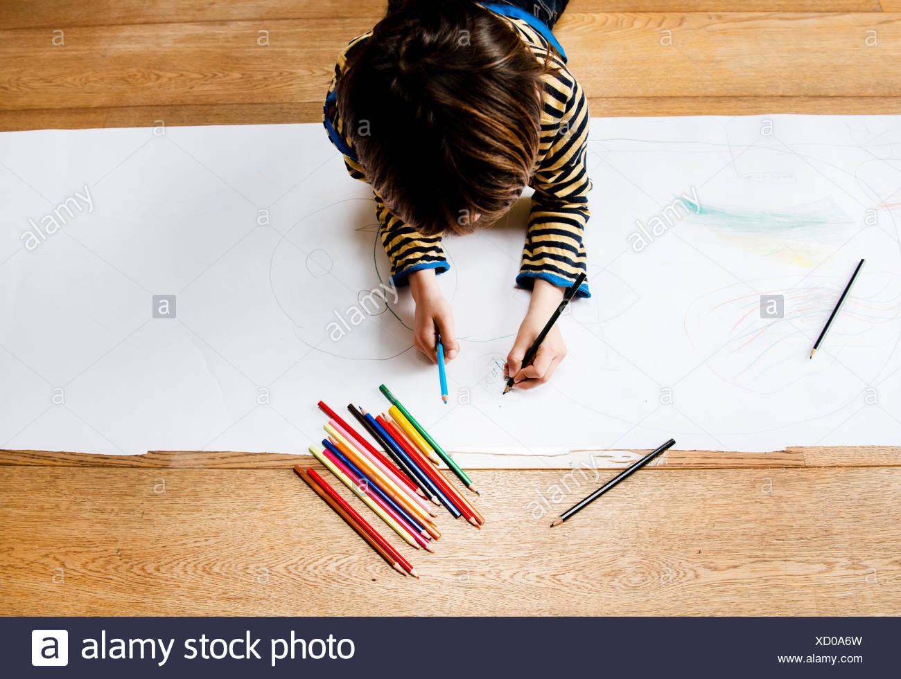 Vista aerea del ragazzo disteso sul pavimento disegno su carta lunga Immagini Stock