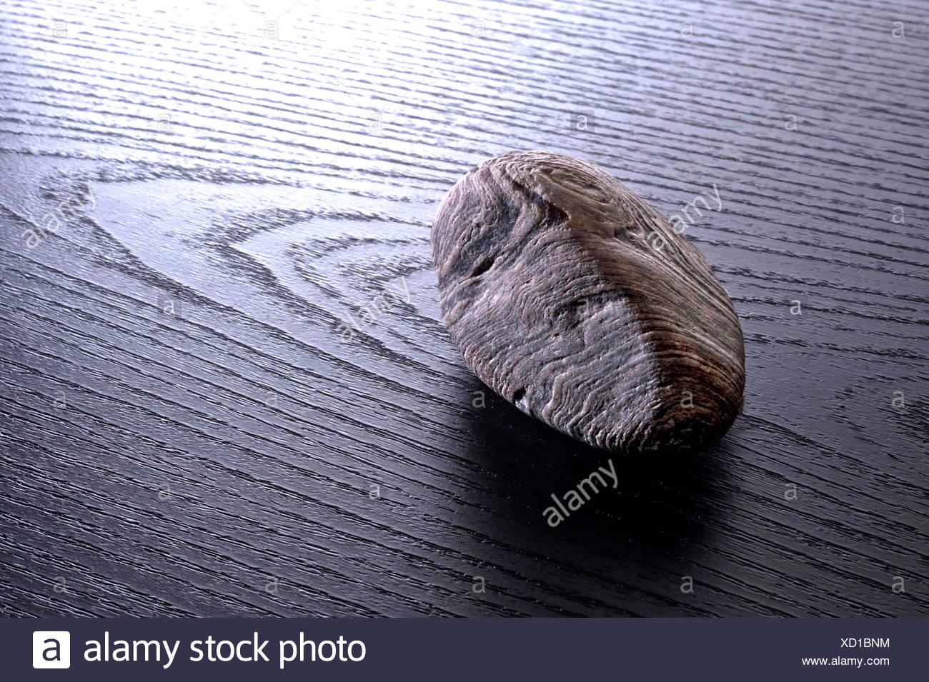 Pietra strutturata giacente sulla grana di legno nero Immagini Stock