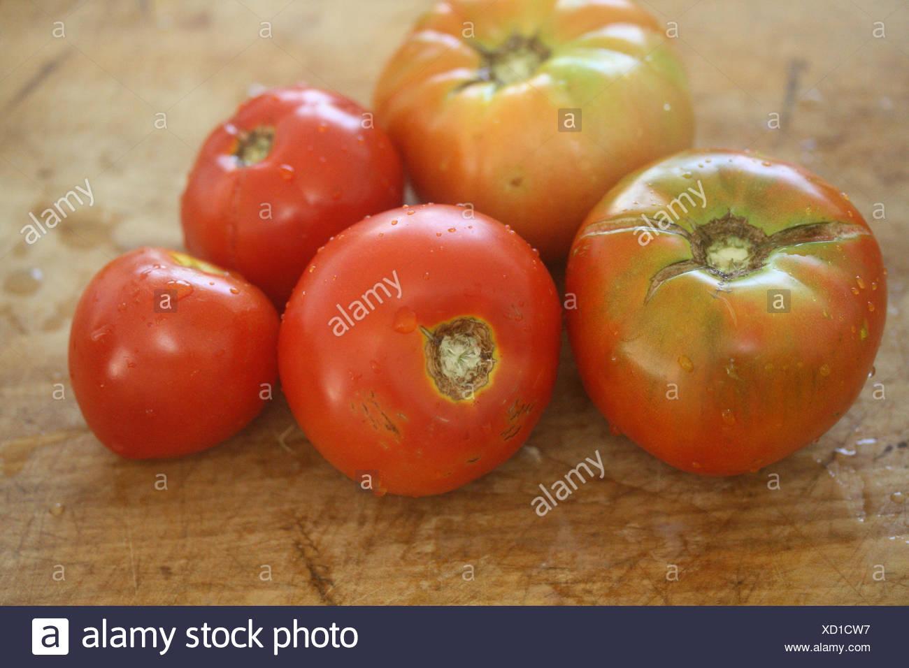 Cinque cimelio di pomodori sul tagliere di legno Immagini Stock