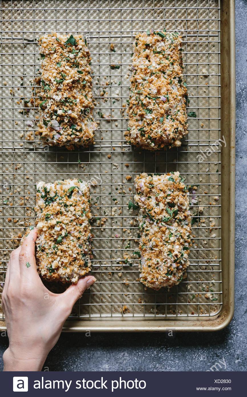 Passo 4 di 4 Una donna è la collocazione dei filetti di pesce impanati su una placca da forno. Immagini Stock