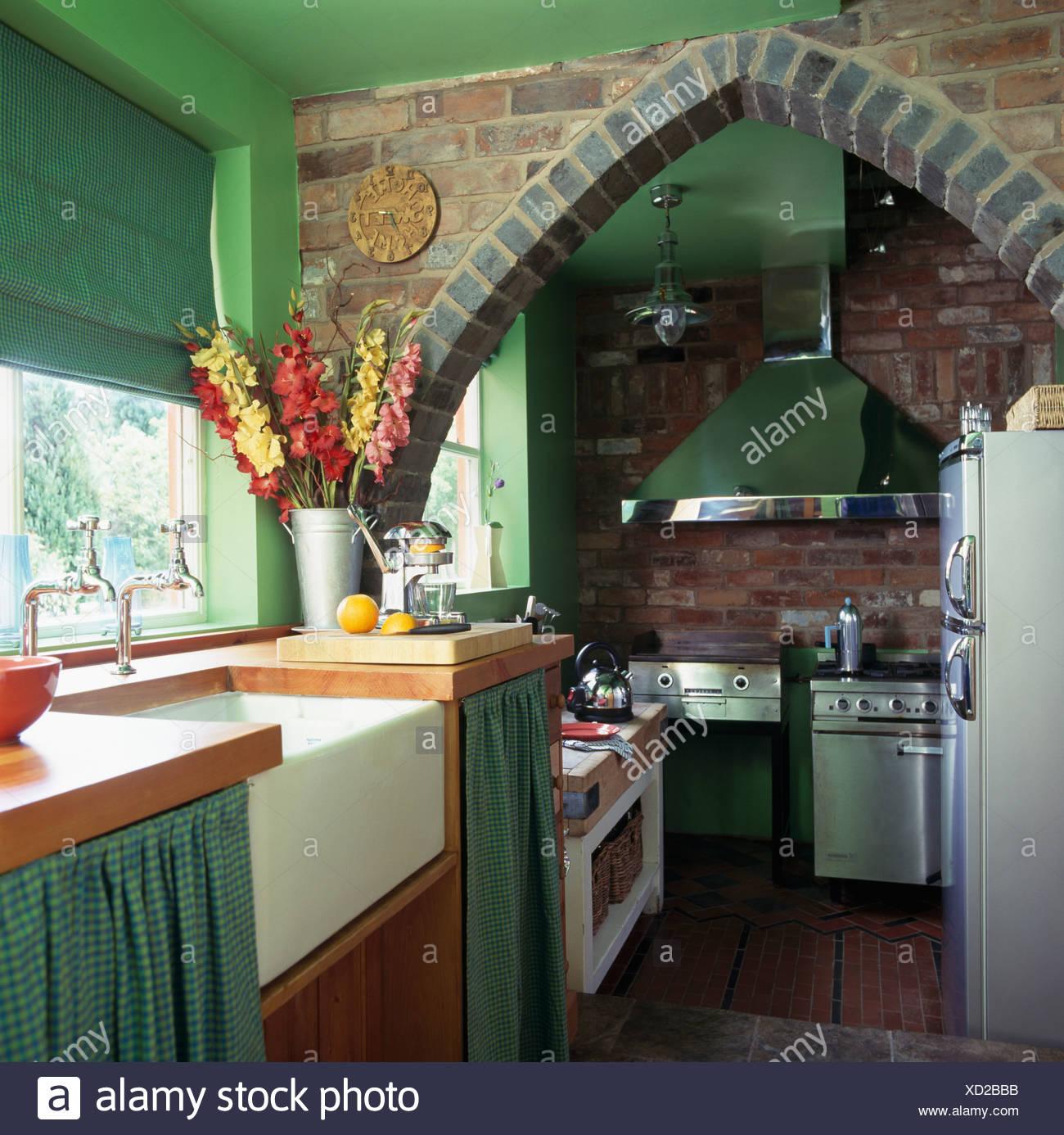 Arco in mattoni nella piccola cucina verde con verde cieco sulla ...