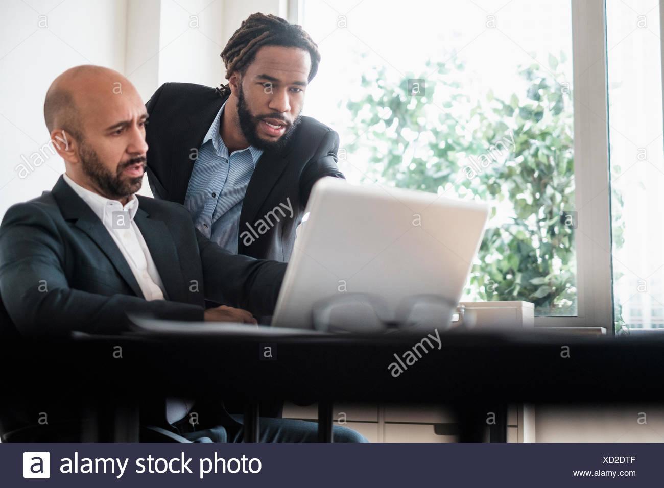 Due imprenditori lavora con il computer portatile da scrivania in ufficio Immagini Stock