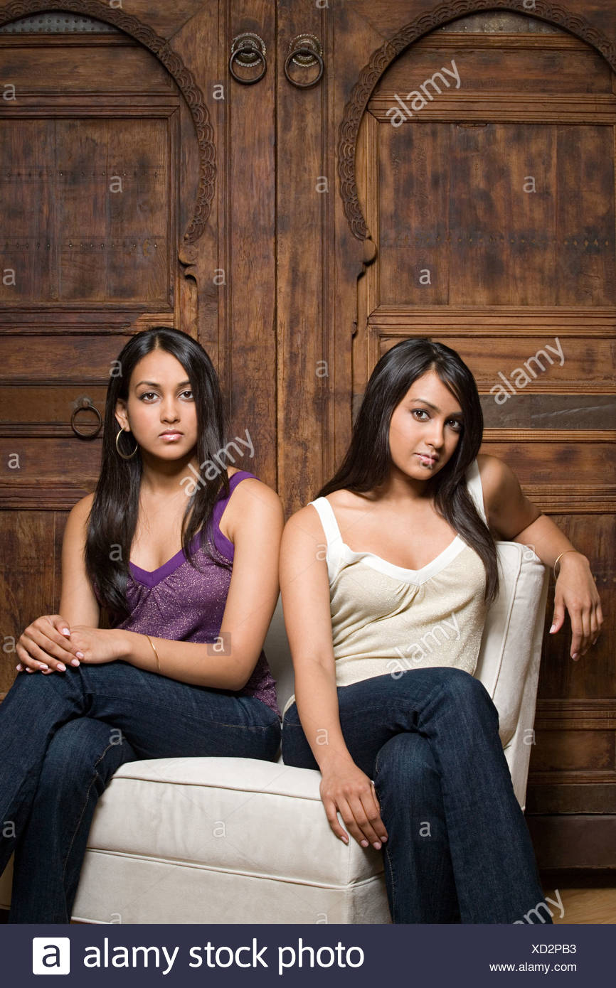 Indian sorelle che condividono una sedia Immagini Stock
