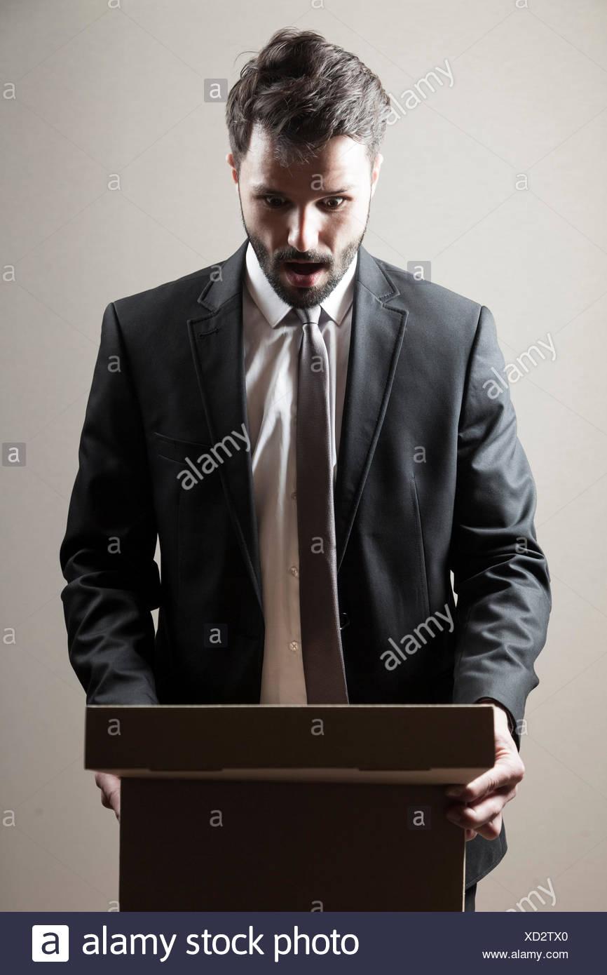 Imprenditore guardando la scatola di cartone bocca aperta Immagini Stock