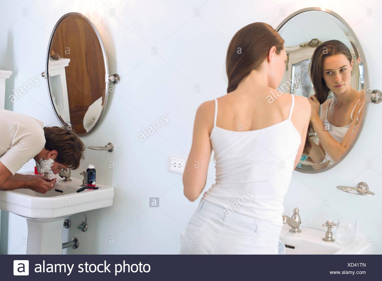 Donna capelli di spazzolatura, marito la rasatura Immagini Stock