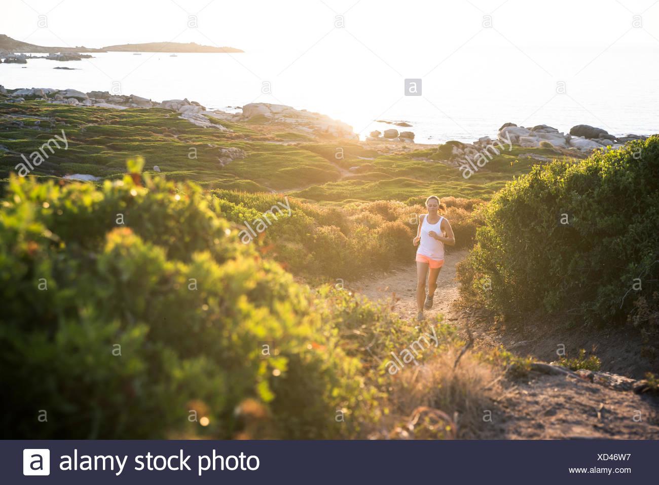 Francia, Corsica, Donna trail running a costa Immagini Stock