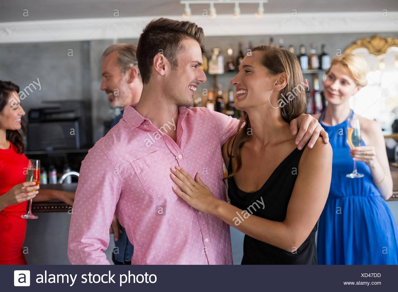 Giovane che abbraccia ogni altra in ristorante Immagini Stock