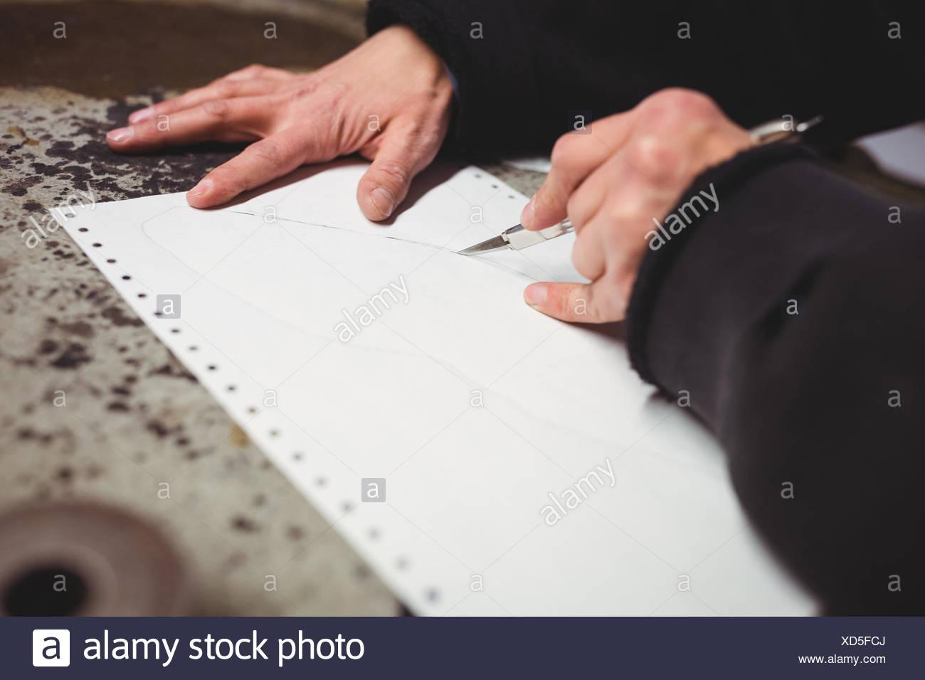 Il comando cobbler il taglio di un foglio di carta Immagini Stock