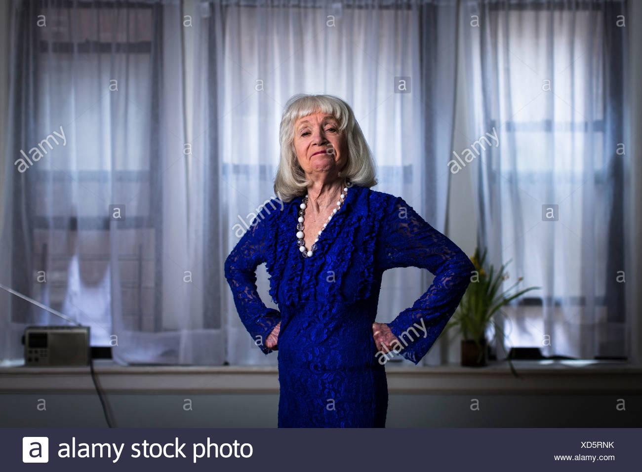 Senior donna in vestito blu con le mani sui fianchi Immagini Stock