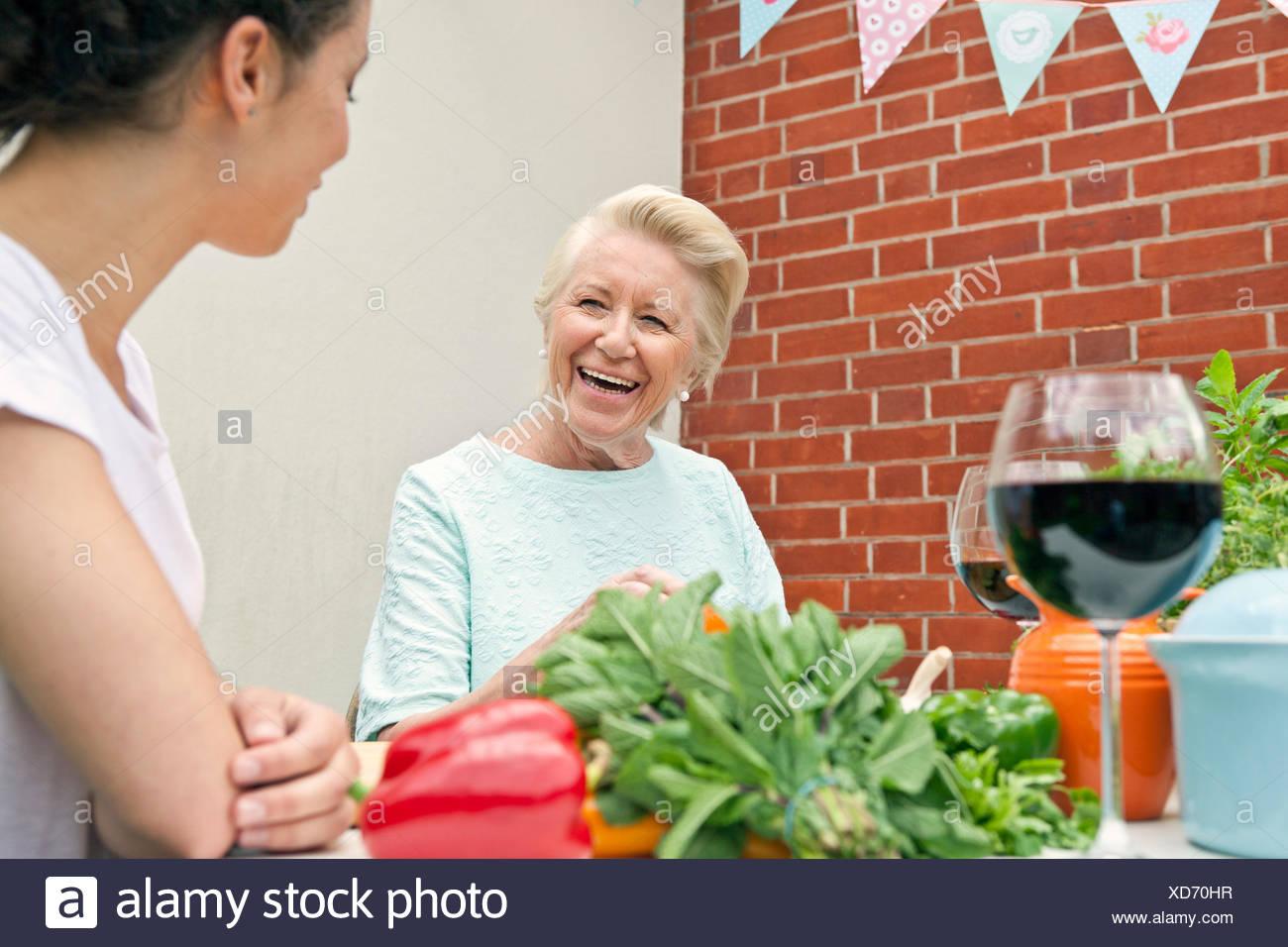 Due donne che chiacchierano mentre prepara il cibo al tavolo da giardino Immagini Stock