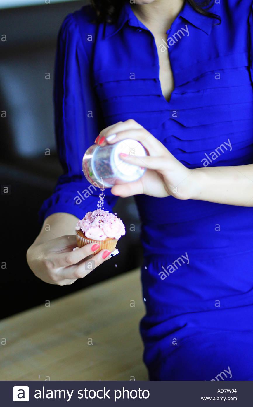 Donna in vestito blu mette topping sul cupcake, Copenhagen, Danimarca Immagini Stock