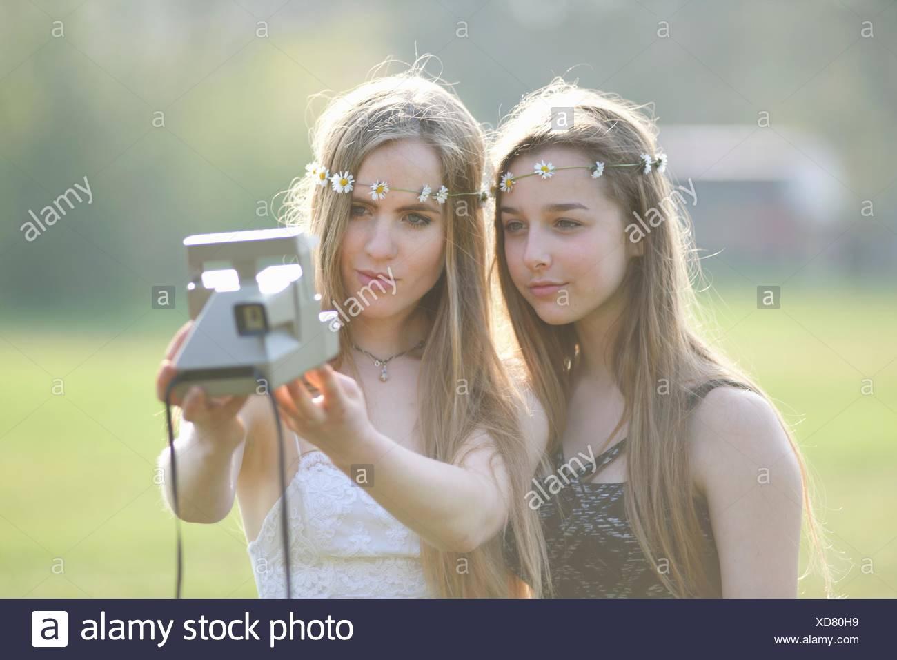 Due ragazze adolescenti in stazionamento tenendo la fotocamera istantanea selfie Immagini Stock