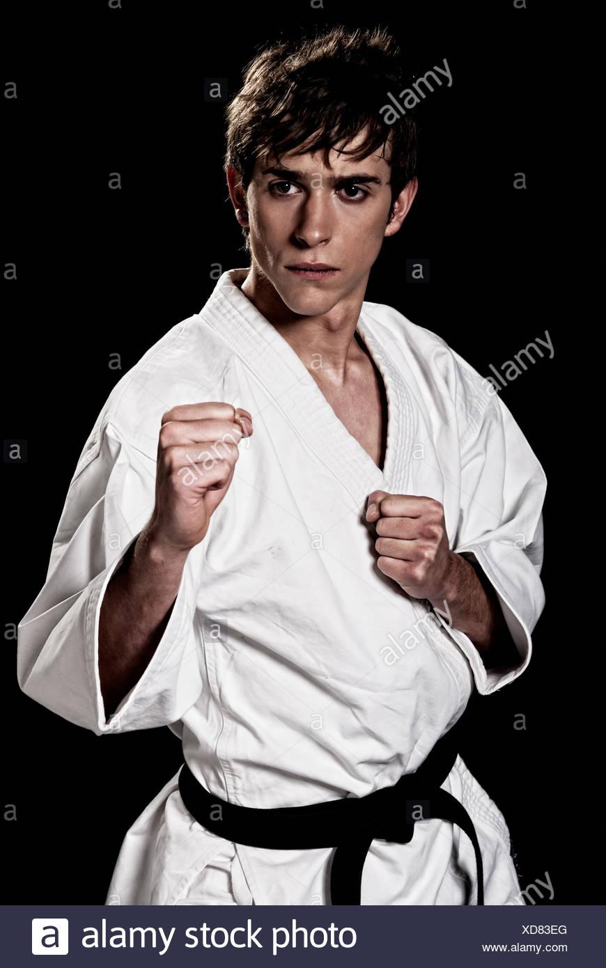 Il Karate fighter maschi giovani e ad alto contrasto su fondo nero Foto Stock