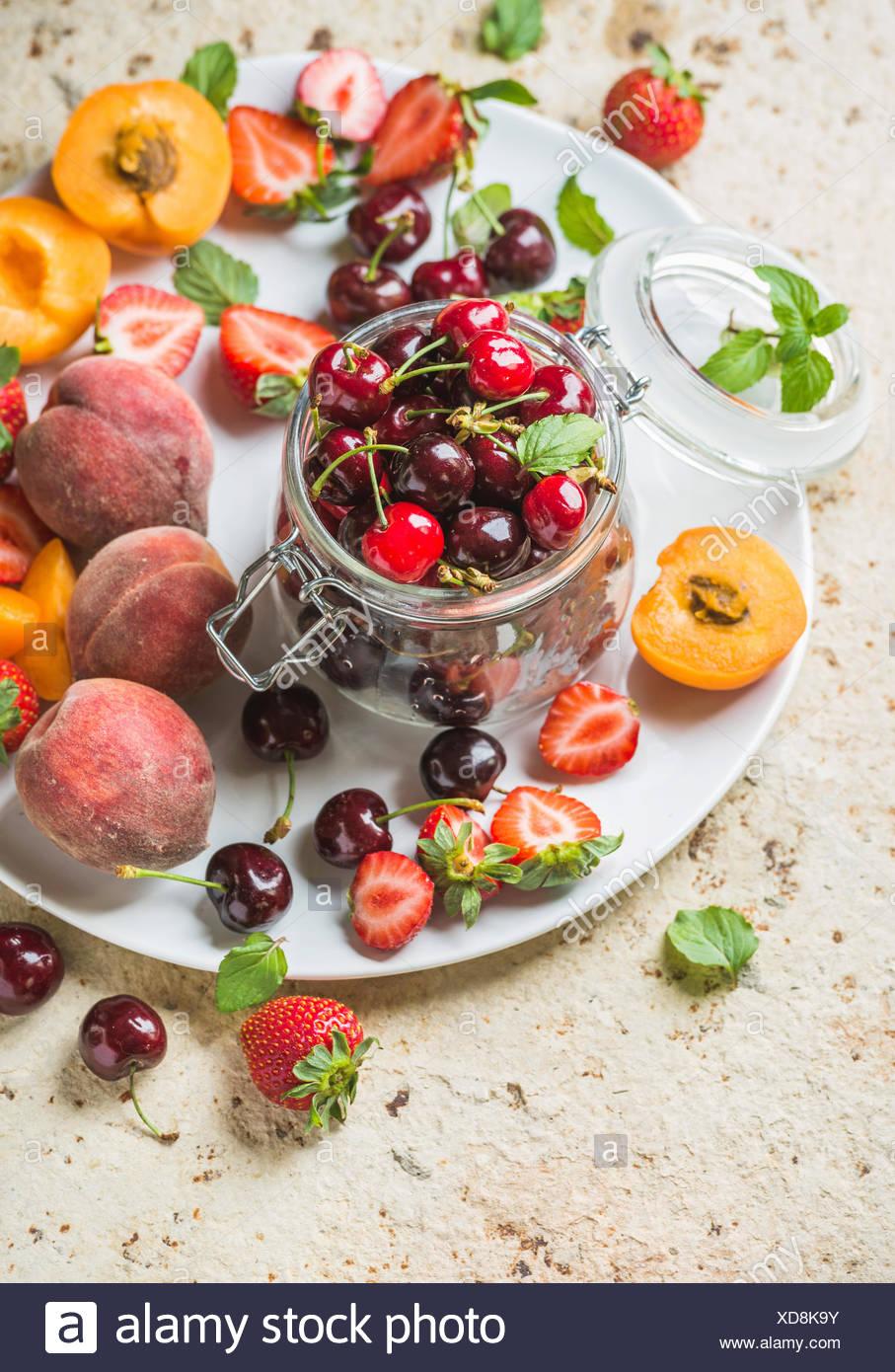 Sana frutta estiva varietà. Dolce di ciliegie, di pesche e fragole su bianco che serve la piastra al di sopra della luce di sfondo di calcestruzzo. Top v Immagini Stock