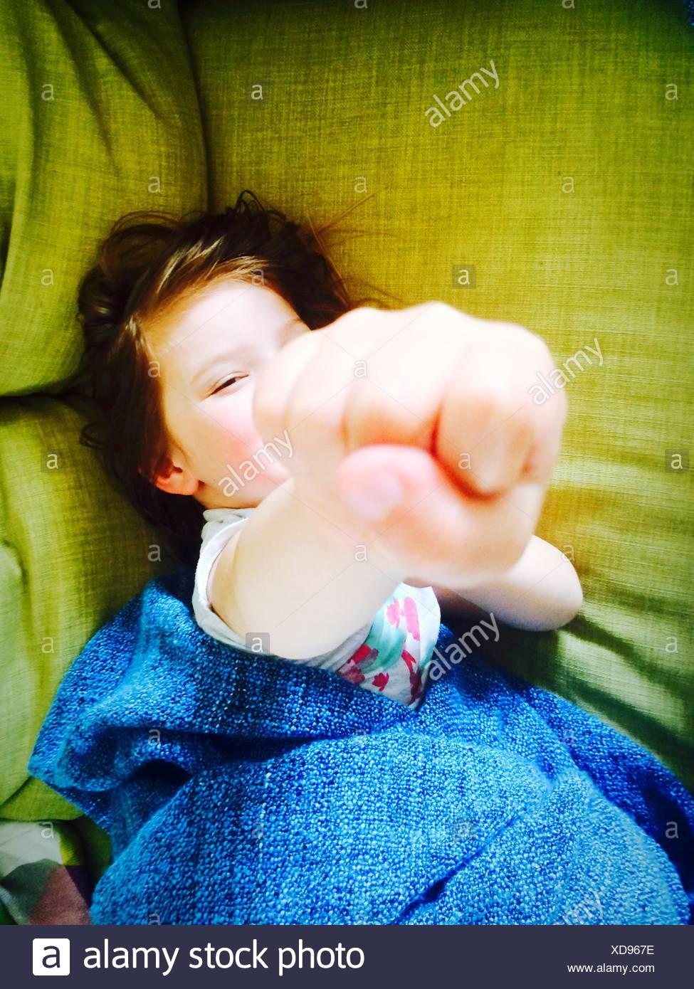 Ritratto di una ragazza che mostra pugno durante i momenti di relax sul letto Immagini Stock