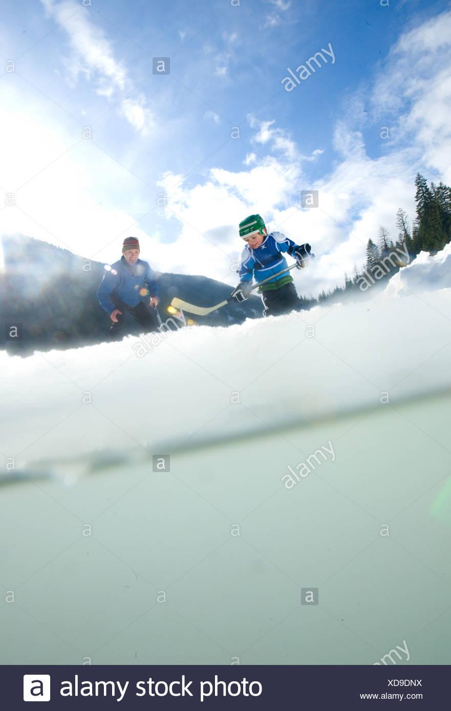Un giovane ragazzo gioca pond hockey con un adulto skater pioppi neri americani sul lago, Nelson, British Columbia, Canada Immagini Stock