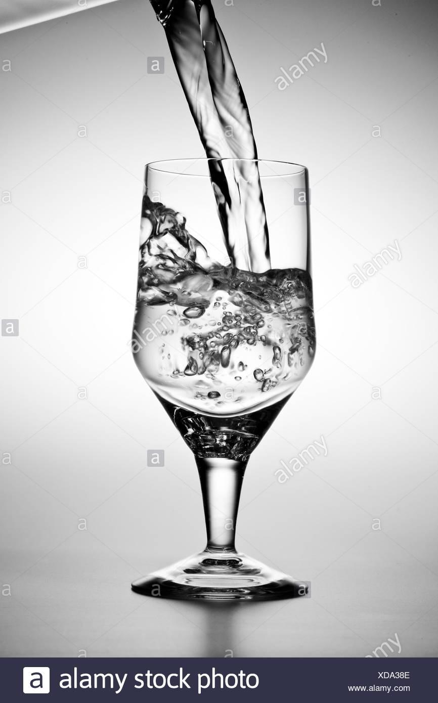 L'acqua viene versata in un bicchiere Foto Stock