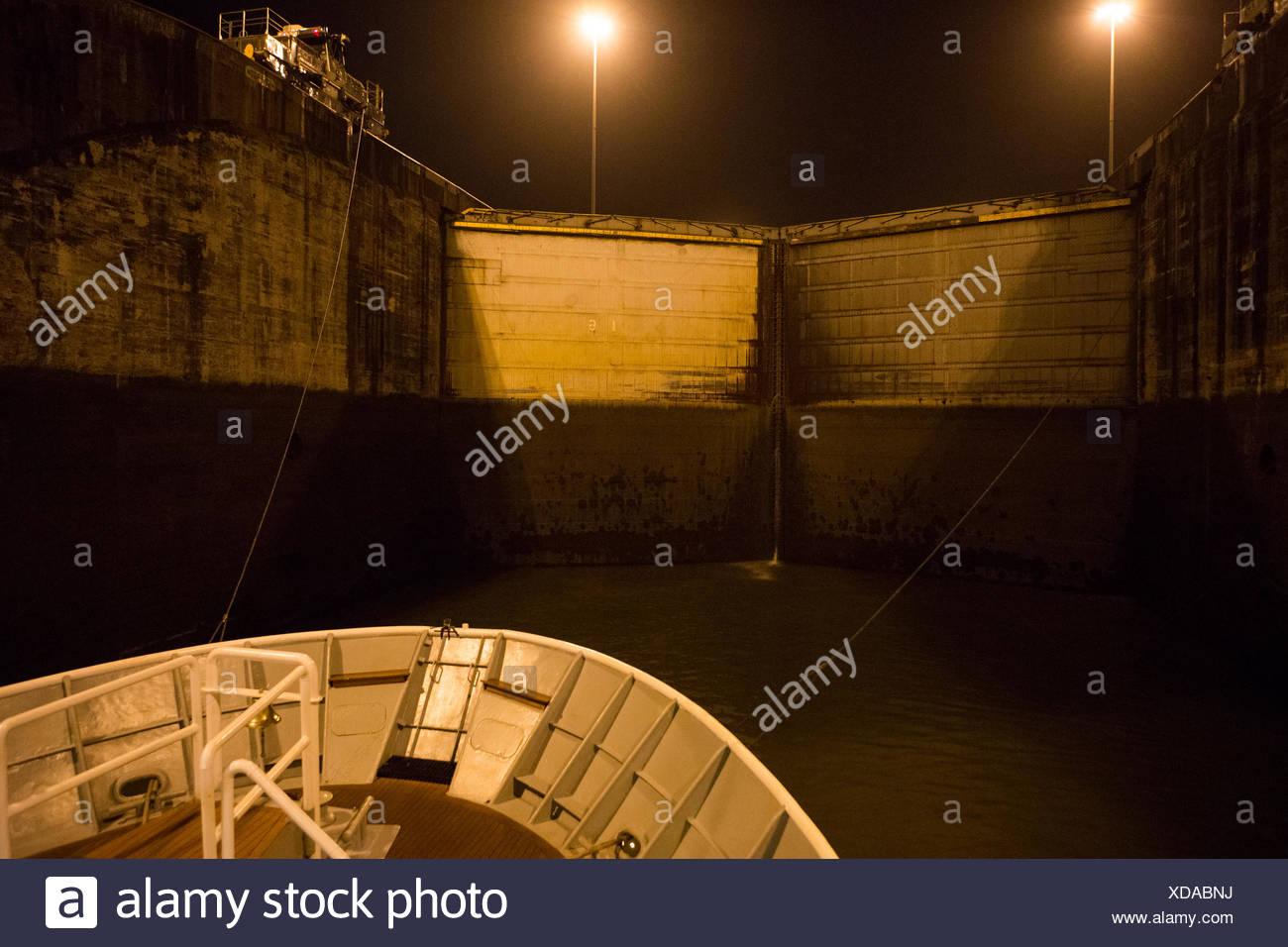 Una barca di crociera è legata al treno di guida motori come la nave entra  serrature Gatun dall Atlantico ingresso del canale di Panama. 4bc4e061197c