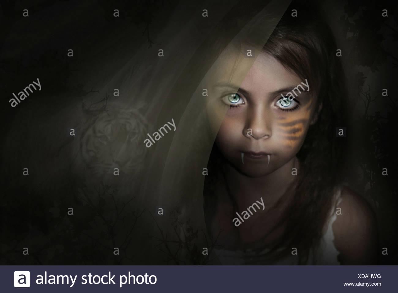 Immagine di fantasia con un giovane bambino con zanne e una tigre lo sfondo dietro di lei. Immagini Stock