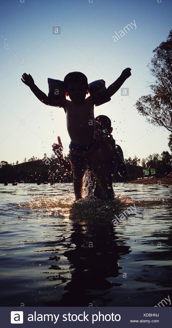 Padre e Figlio godendo nel fiume durante la stagione estiva Immagini Stock
