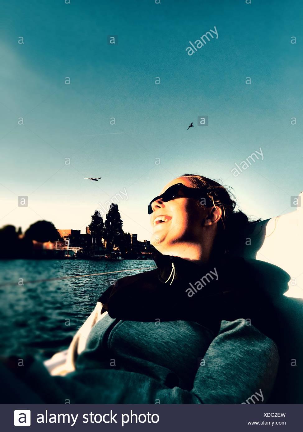 Basso Angolo di visione della donna seduta nel recipiente nautico presso il River Immagini Stock
