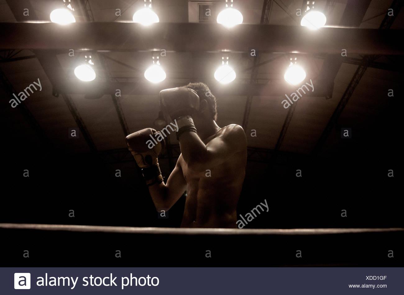Boxer in un anello di inscatolamento con le mani alzate nella parte anteriore del suo volto Immagini Stock