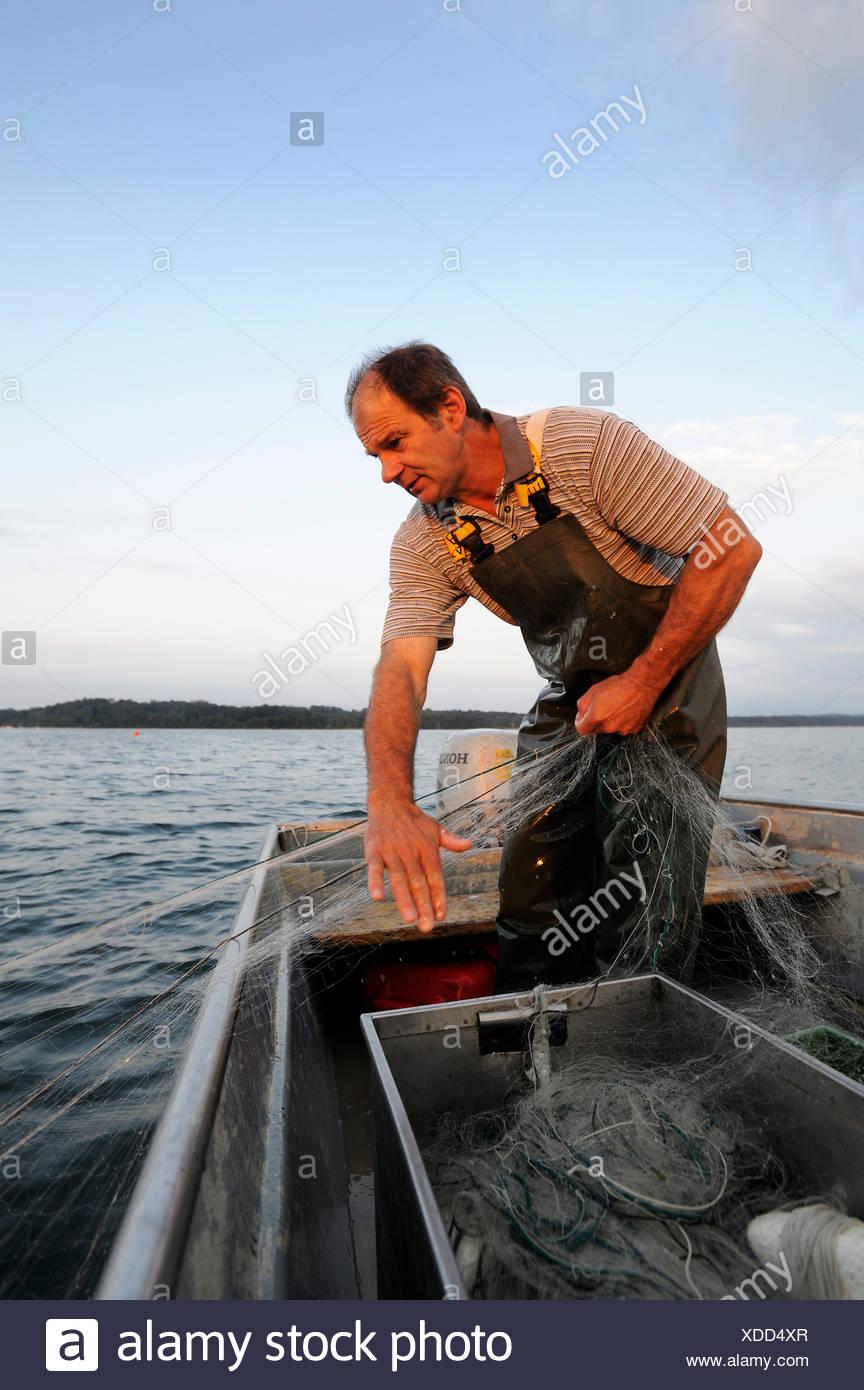 Il pescatore Johann Strobl casting per pescare sul Lago di Starnberg, area Fuenfseenland, Alta Baviera, Baviera Immagini Stock