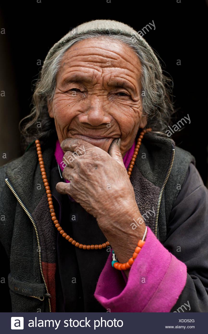 Una vecchia donna adornata con colorati i grani di preghiera e polsini. Immagini Stock